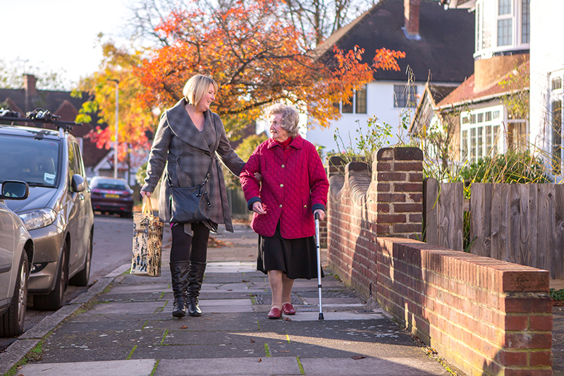 Carer supporting client walking home from shopping trip